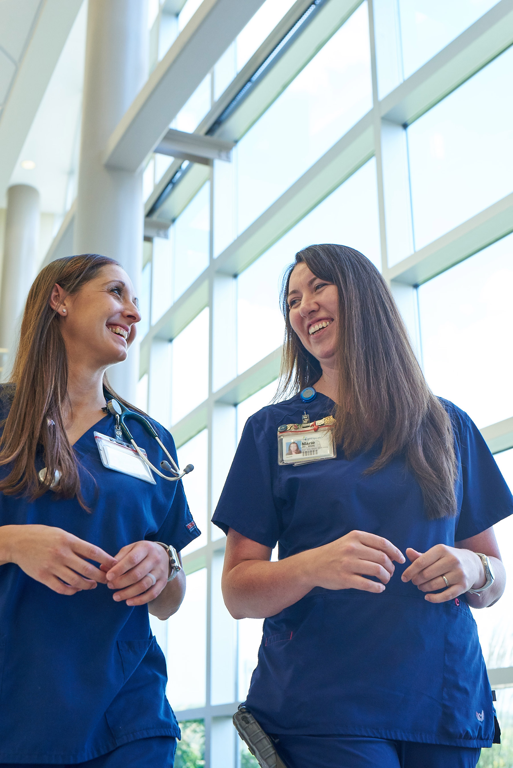 Two young nurses smiling and talking in hallway