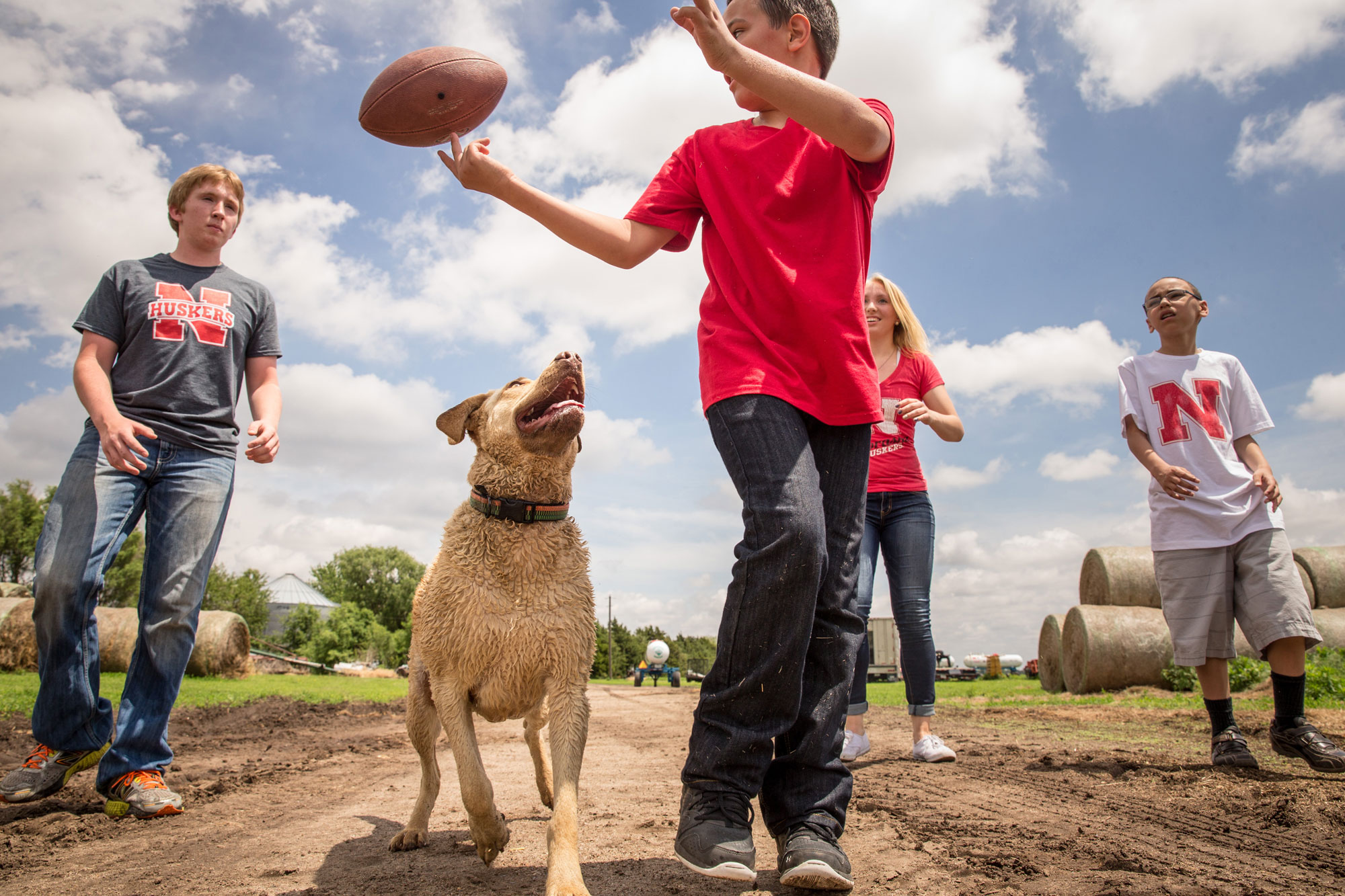 Family with dog throwing football in field.