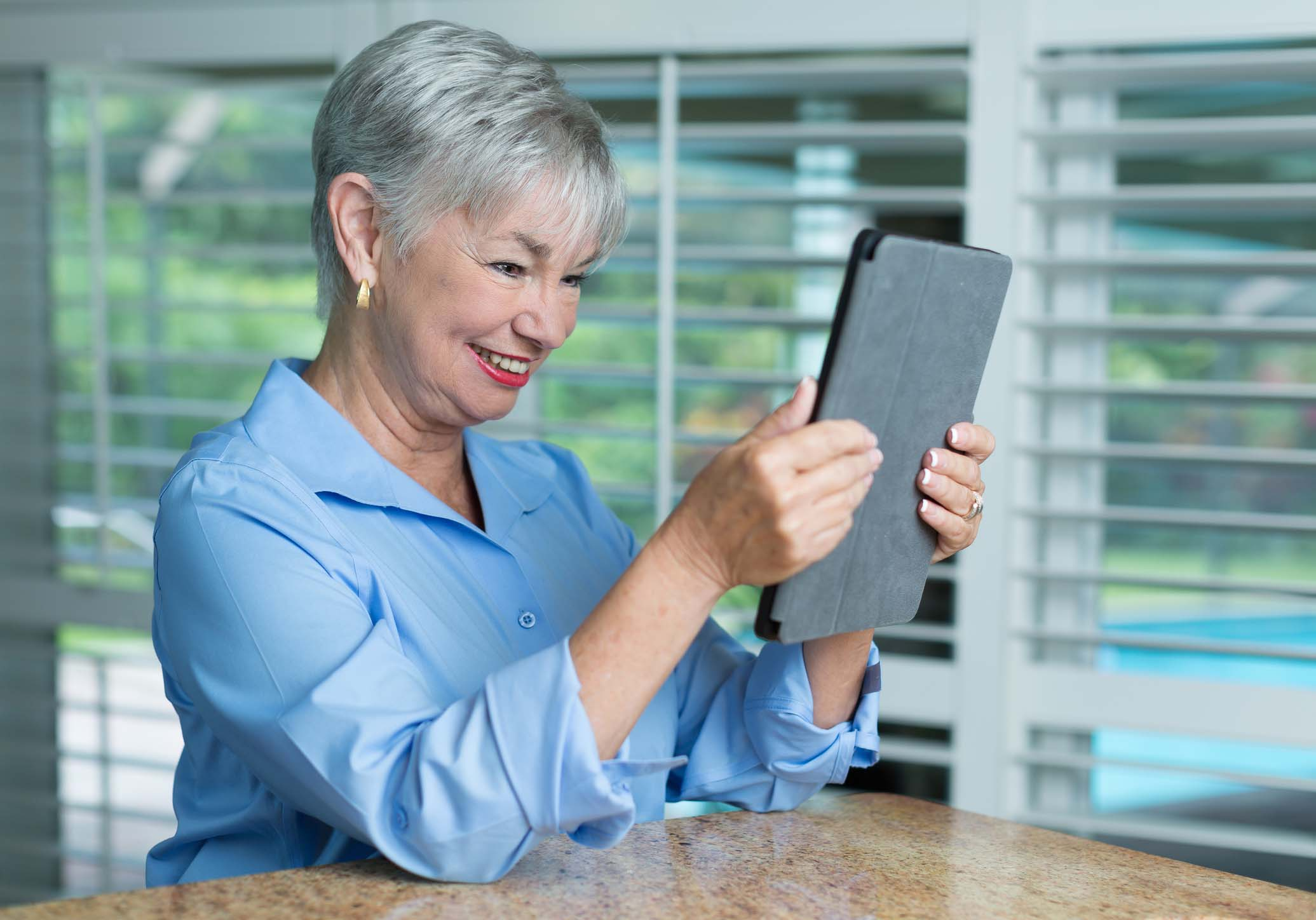 Senior woman checking digital tablet on the kitchen counter
