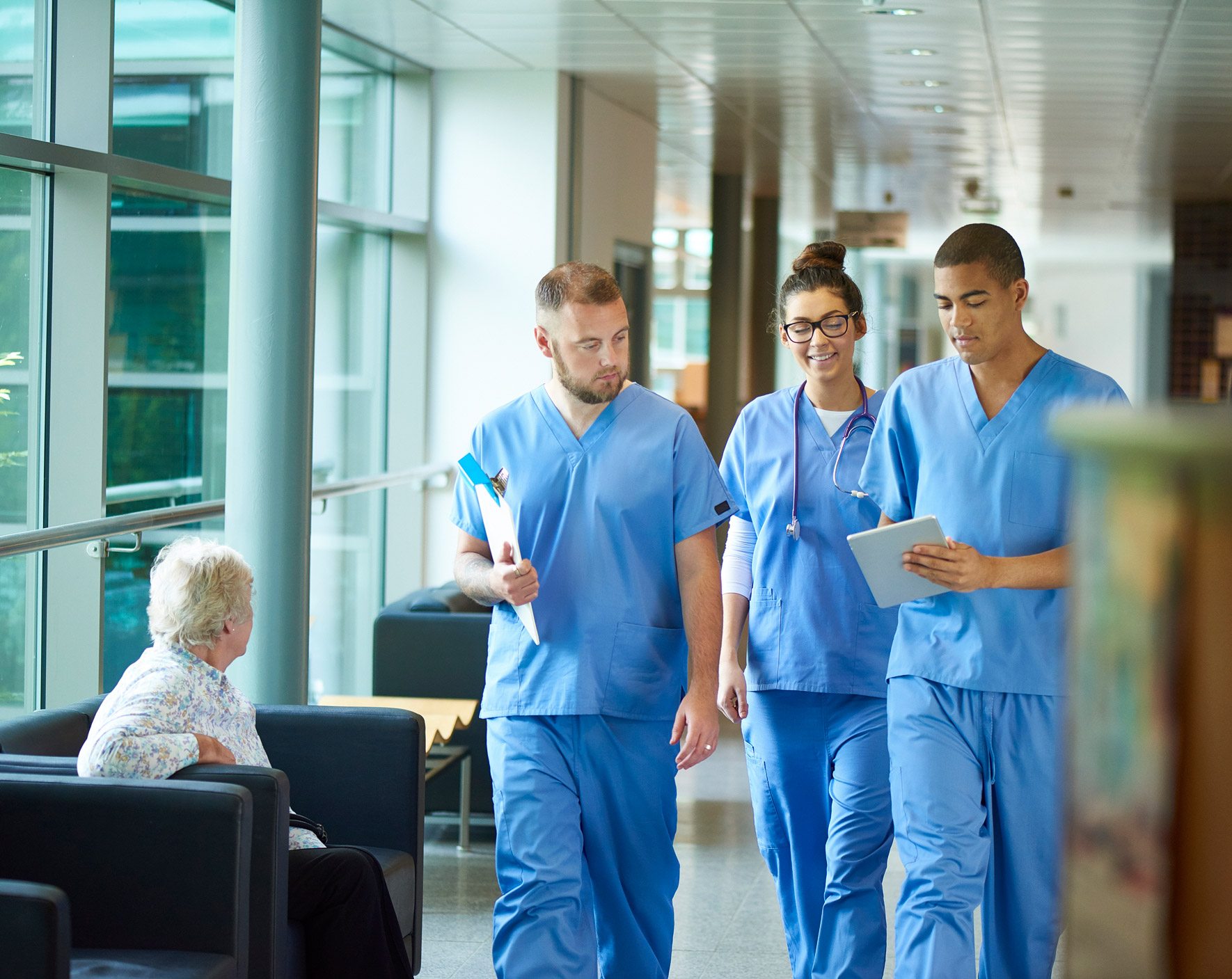 Three nurses walking and talking in a hallway