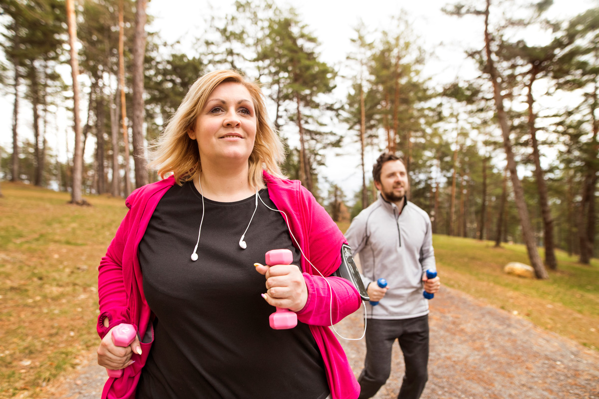 Middle aged woman walking on a forested trail with arm weights